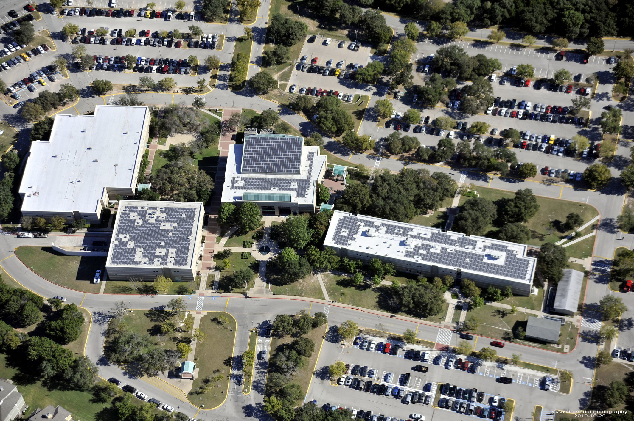 An arial view of Austin Community College buildings toped with solar panels surrounded by parked cars